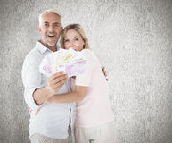 Composite image of happy couple flashing their cash Royalty Free Stock Images