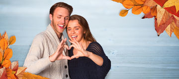 Composite image of happy couple forming heart with hands Stock Photo