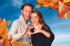 Composite image of happy couple forming heart with hands Stock Photos