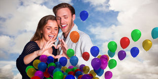 Composite image of happy couple forming heart with hands Stock Photography