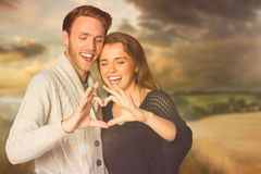 Composite image of happy couple forming heart with hands Royalty Free Stock Photo