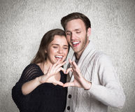Composite image of happy couple forming heart with hands Royalty Free Stock Image