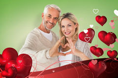 Composite image of happy couple forming heart shape with hands. Happy couple forming heart shape with hands against green vignette stock image