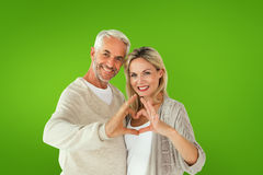 Composite image of happy couple forming heart shape with hands Royalty Free Stock Photography