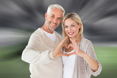 Composite image of happy couple forming heart shape with hands Royalty Free Stock Images