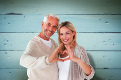 Composite image of happy couple forming heart shape with hands Stock Images