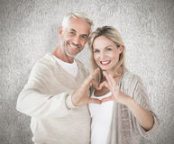 Composite image of happy couple forming heart shape with hands Royalty Free Stock Image