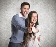 Composite image of happy couple gesturing thumbs up Stock Images