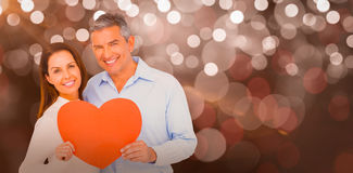 Composite image of happy couple holding big heart shape paper Royalty Free Stock Photos