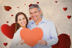 Composite image of happy couple holding big heart shape paper Stock Photo