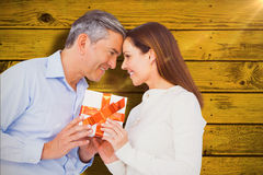 Composite image of happy couple holding gift Royalty Free Stock Images