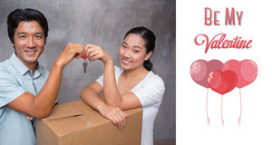 Composite image of happy couple holding house key and leaning on moving box Stock Photography