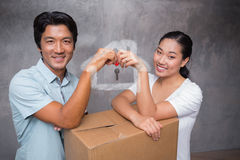 Composite image of happy couple holding house key and leaning on moving box Stock Image