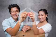 Composite image of happy couple holding house key and leaning on moving box Stock Images