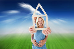 Composite image of happy couple holding house outline Stock Photos