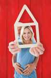 Composite image of happy couple holding house outline Stock Photography