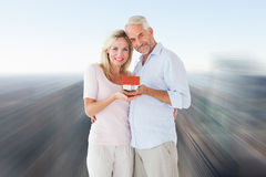 Composite image of happy couple holding miniature model house Royalty Free Stock Image