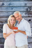 Composite image of happy couple holding miniature model house Stock Image