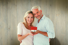 Composite image of happy couple holding miniature model house Stock Photos
