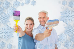 Composite image of happy couple holding paintbrushes smiling at camera Stock Images