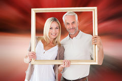 Composite image of happy couple holding a picture frame Stock Photos