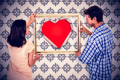Composite image of happy couple holding picture frame Stock Image