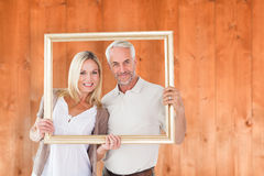 Composite image of happy couple holding a picture frame Stock Photo
