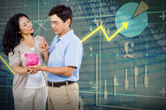Composite image of happy couple holding a piggy bank stock photos