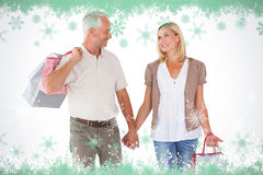 Composite image of happy couple holding shopping bags and hands Stock Photos