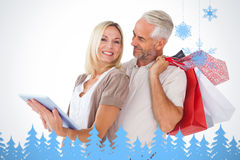 Composite image of happy couple holding shopping bags and looking at tablet pc Royalty Free Stock Images
