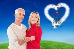 Composite image of happy couple holding their hands out Royalty Free Stock Image