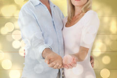 Composite image of happy couple holding their hands out Royalty Free Stock Photo