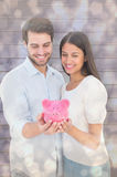Composite image of happy couple holding their piggy bank Stock Images