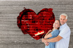 Composite image of happy couple hugging and holding paint roller Stock Images