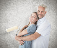 Composite image of happy couple hugging and holding paint roller Royalty Free Stock Image