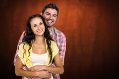 Composite image of happy couple hugging and looking at camera. Happy couple hugging and looking at camera against shades of brown Stock Images
