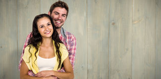 Composite image of happy couple hugging and looking at camera. Happy couple hugging and looking at camera against wooden planks Royalty Free Stock Photos