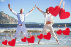 Composite image of happy couple jumping on the beach together Stock Images