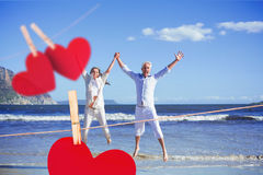 Composite image of happy couple jumping up barefoot on the beach Royalty Free Stock Photos