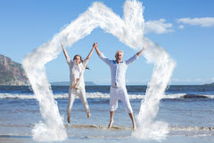 Composite image of happy couple jumping up barefoot on the beach Royalty Free Stock Photo