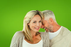 Composite image of happy couple laughing together woman looking at camera. Happy couple laughing together women looking at camera against green vignette Stock Images