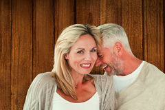Composite image of happy couple laughing together woman looking at camera. Happy couple laughing together women looking at camera against wooden planks Stock Photography
