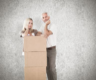 Composite image of happy couple leaning on pile of moving boxes Royalty Free Stock Photos