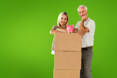 Composite image of happy couple leaning on pile of moving boxes with piggy bank Royalty Free Stock Photo