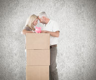 Composite image of happy couple leaning on pile of moving boxes with piggy bank Stock Photos