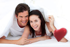 Composite image of happy couple lying on bed Royalty Free Stock Photos