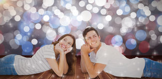 Composite image of happy couple lying on floor and looking away Royalty Free Stock Photography
