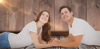 Composite image of happy couple lying on floor and looking up Stock Photo