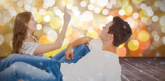 Composite image of happy couple lying on floor and pointing up Royalty Free Stock Photography