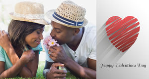 Composite image of happy couple lying in garden together smelling flowers. Happy couple lying in garden together smelling flowers against cute valentines message Stock Photos